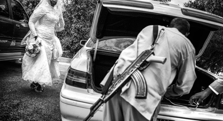 A security guard is fixing the trunk of the car before the bride and the groom leave for their portrait session. Security in Somaliland has been reinforced after the 2008 bombing that targeted the presidential palace, the Ethiopian consulate, and the United Nations Development Program offices in Hargeisa; more than twenty perished.