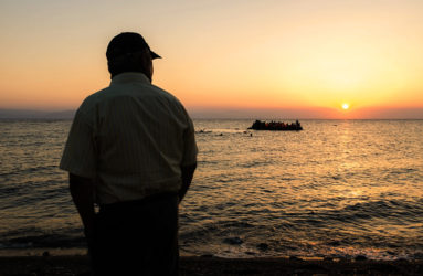 An old man is looking at a dinghy getting closer to the shore in the early morning. In recent weeks on Kos island, locals have been witnessing the arrival, by sea from Turkey, of an average of 600 people every day, according to the UNHCR.