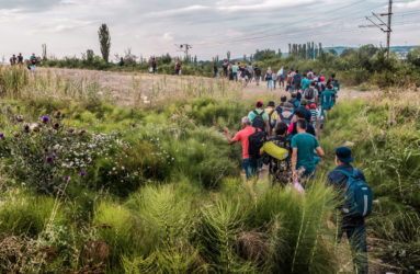 A group of refugees is illegally crossing through the open border into Serbia.