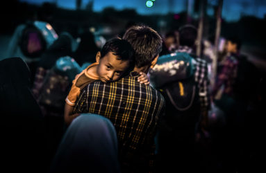 A young child rests on his father's shoulder after a few hundred refugees disembark from a train, which arrived from Gevgelija. This group of refugees is making their way towards Serbia on foot.