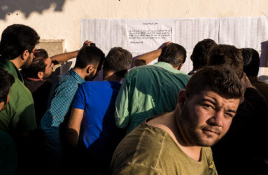 A group of men are looking for their names on the list outside the Police Station in the town of Kos. The process for issuing travel documents has been streamlined by the Greek authorities.