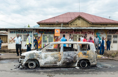 A burned car and a dead body in the streets of Mutakura. In the morning, residents routinely discover the damages of the previous night.